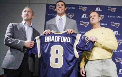 St. Louis Rams quarterback Sam Bradford, center, holds up his new jersey along side Rams head coach Steve Spagnuolo, left, and general manager Billy Devaney, right, before speaking to the media during an NFL news conference on Friday, April 23, 2010, in St. Louis. Bradford was selected as the No. 1 overall pick by the Rams in the first round.