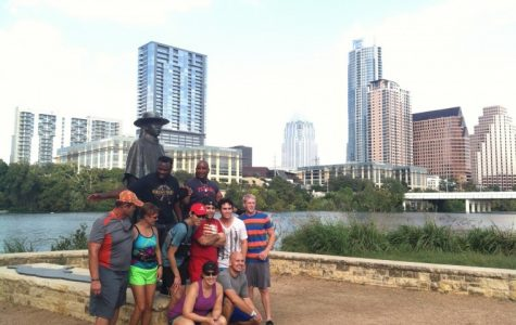 Participants on an Austin running tour pause for a photo with the iconic statue of Stevie Ray Vaughan on Lady Bird Lake.