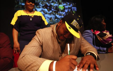 Cass Tech. senior David Dawson signs his letter of intent to play football at the University of Michigan during National Signing Day activities in Detroit, Michigan, Wednesday, February 6, 2013.