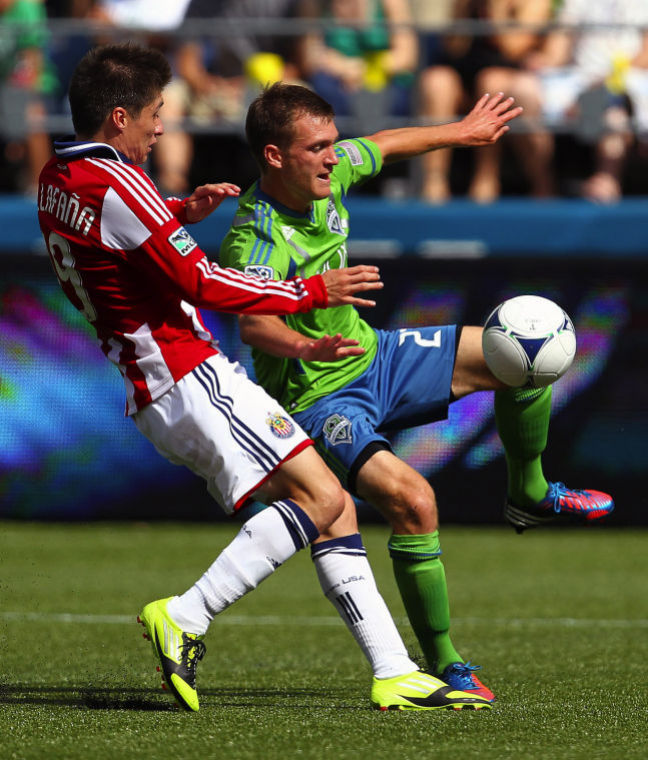 Sounders FC midfielder Alex Caskey, right, attempts to trap a teammate's pass as Chivas USA player Jorge Villafana, left, battles for possession during the second half at CenturyLink Field in Seattle, Washington, Saturday, September 8, 2012. Sounders FC defeated Chivas USA, 2-1.