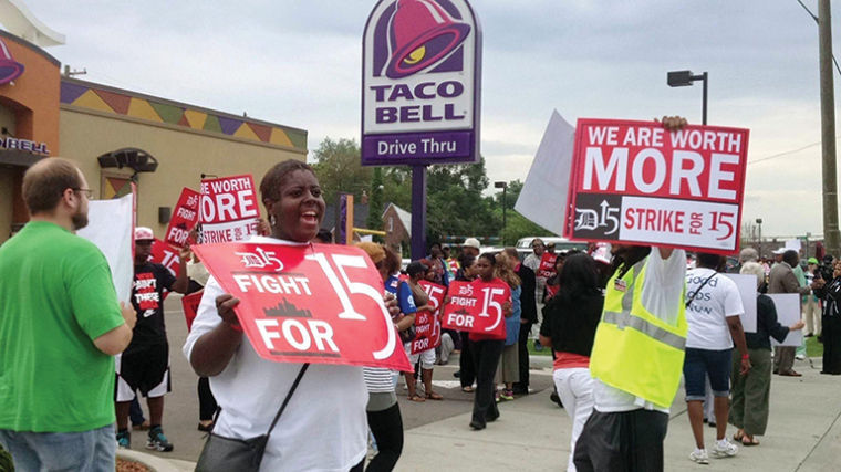 Fast+food+employees+rally+outside+a+restaurant+in+hopes+of+receiving+an+increased+wage.