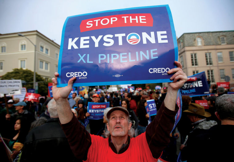 John McCullough holds up his sign protesting the plan to build an oil pipeline from Canada to Texas, called the Keystone XL pipeline, in San Francisco, California, on Wednesday, April 3, 2013.