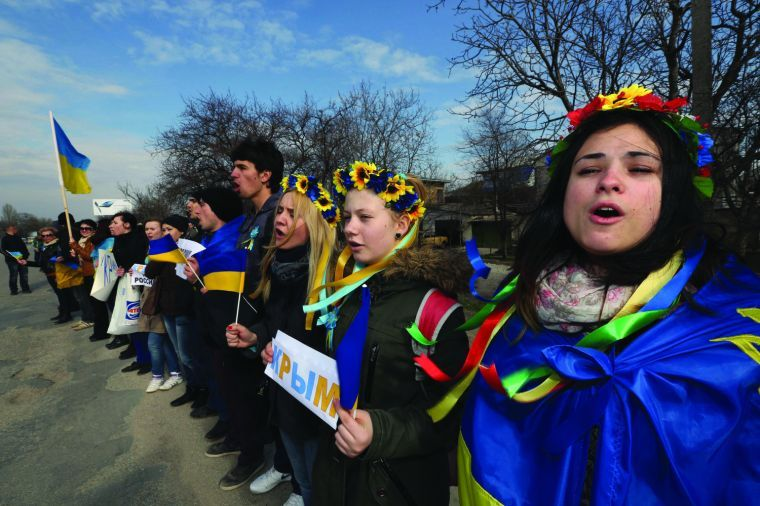 Anti-war demonstrators sing Ukraine's national anthem during a protest action in Simferopol, Ukraine, on Friday, March 14, 2014.