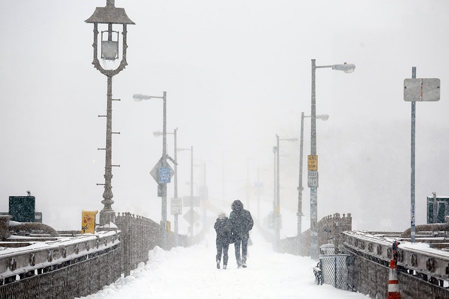A couple walks across the Brooklyn Bridge in New York on Saturday, Jan. 23, 2016, during a powerful weekend storm blanketing the East Coast in snow. (Carolyn Cole/Los Angeles Times/TNS)