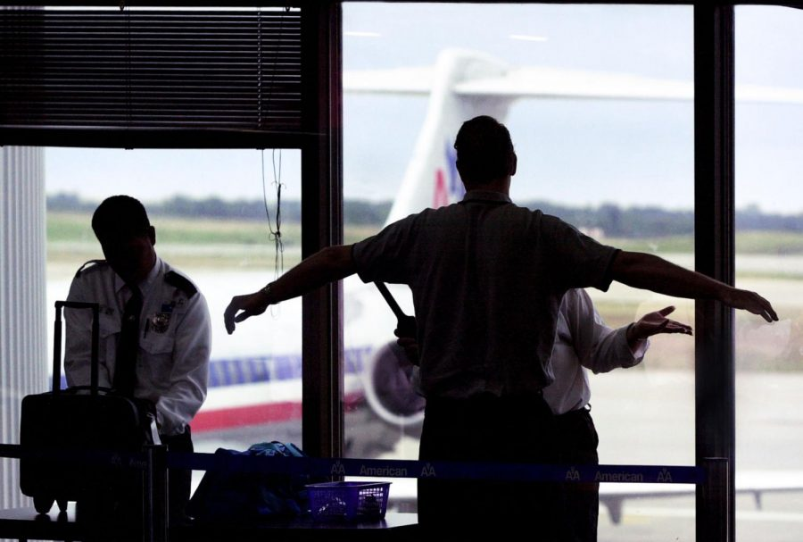 Security personnel at American Airlines screen a passenger prior to boarding, Tuesday, August 13, 2002, at Kansas City International Airport in Kansas City, Missouri.