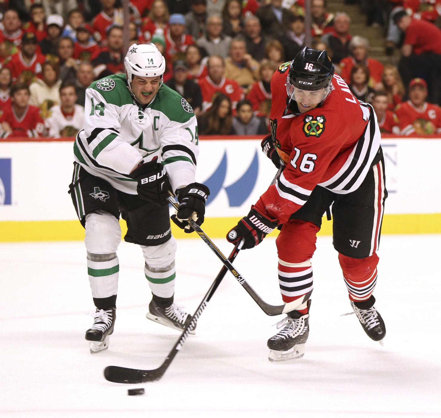 Chicago Blackhawks left wing Andrew Ladd (16) shoots the pack away from Dallas Stars left wing Jamie Benn (14) during the first period of their game on March 22, 2016 at the United Center in Chicago. (Nuccio DiNuzzo/Chicago Tribune/TNS)
