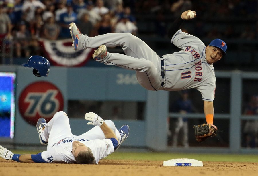 The Los Angeles Dodgers' Chase Utley upends New York Mets shortstop Ruben Tejada (11) to break up a potential double play in the seventh inning at Dodger Stadium in Los Angeles on Saturday, Oct. 10, 2015. (Robert Gauthier/Los Angeles Times/TNS)