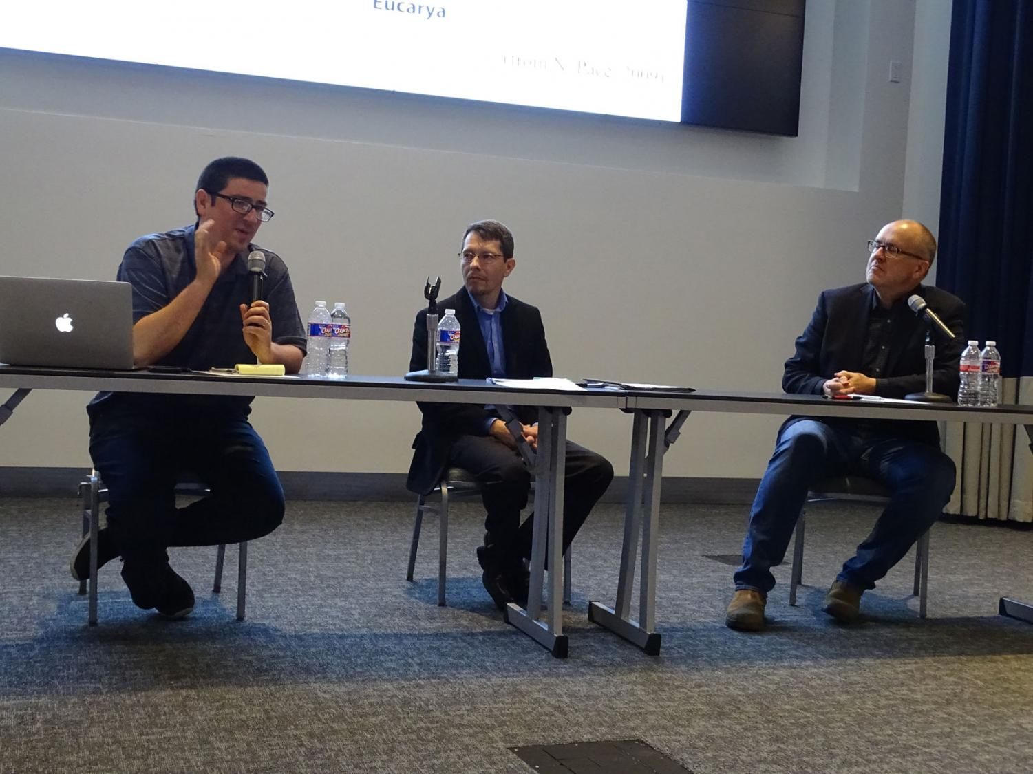 Joel Velasco, left, Stephen Dilley, center, and Paul Nelson, right, at a debate about Darwin's evolution theory Oct. 21.