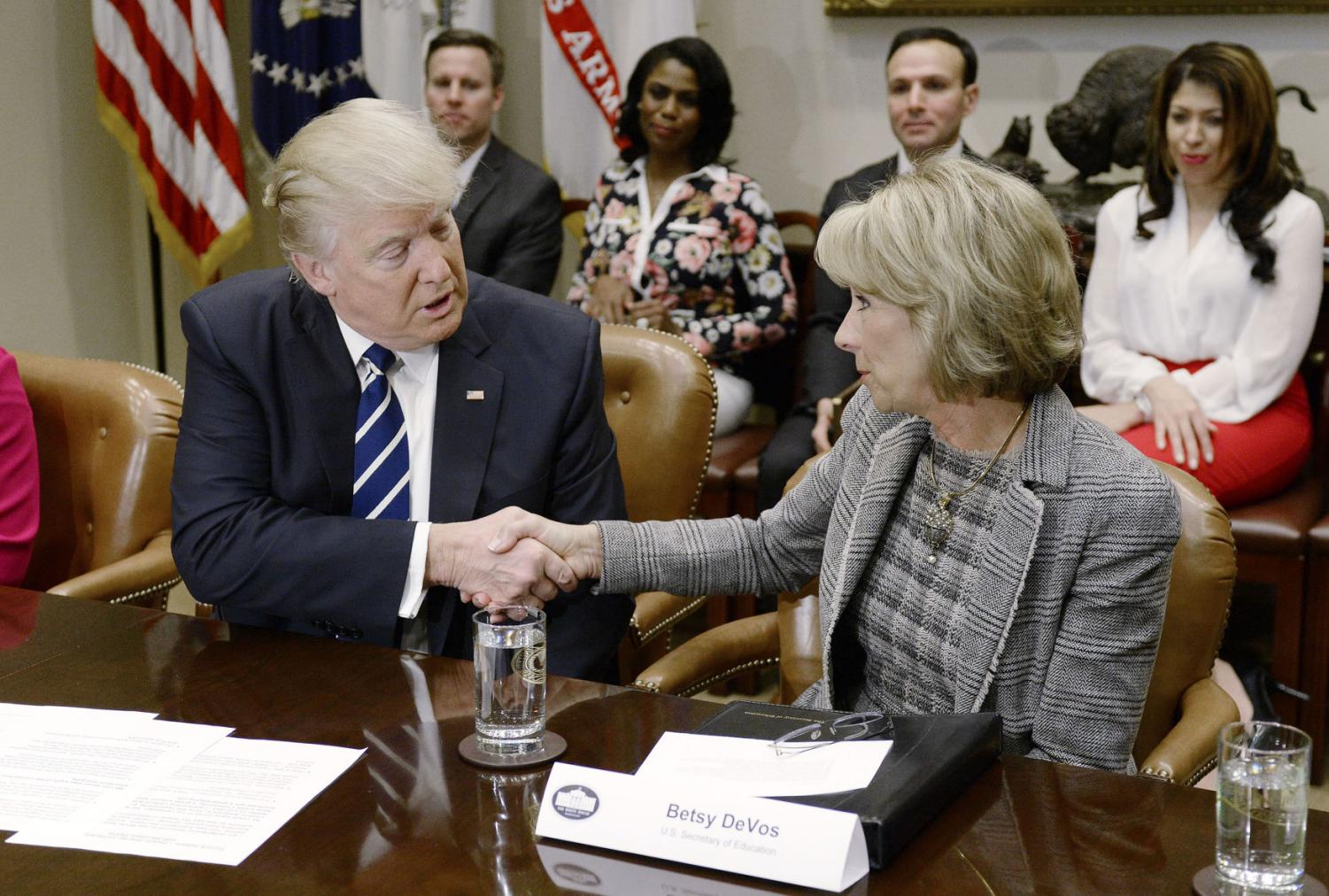 President Donald Trump congratulates Education Secretary Betsy DeVos during a parent-teacher conference listening session in the Roosevelt Room of the White House Feb. 14 in Washington.