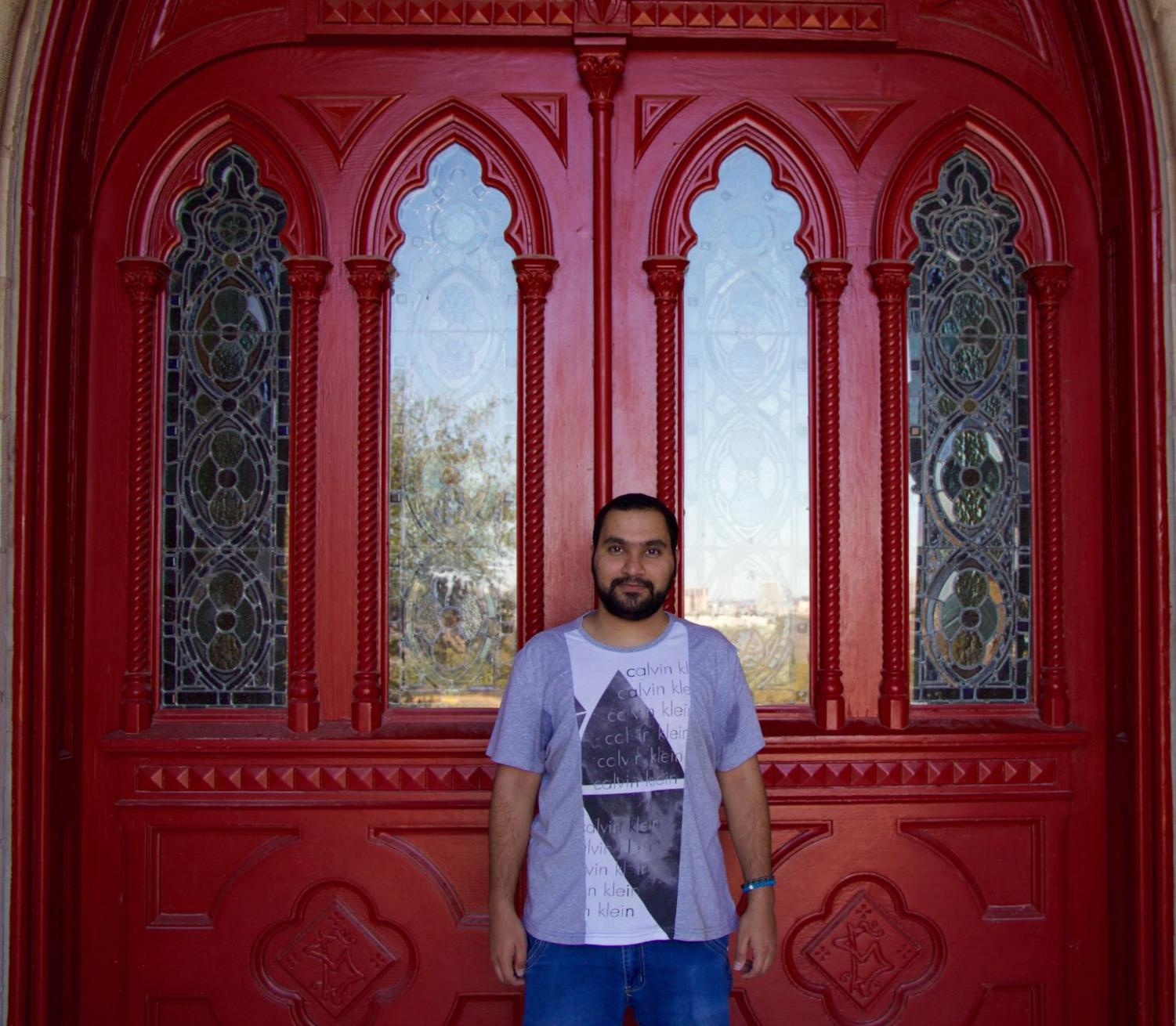 International student Omar Alazmi stands in front of the red doors.