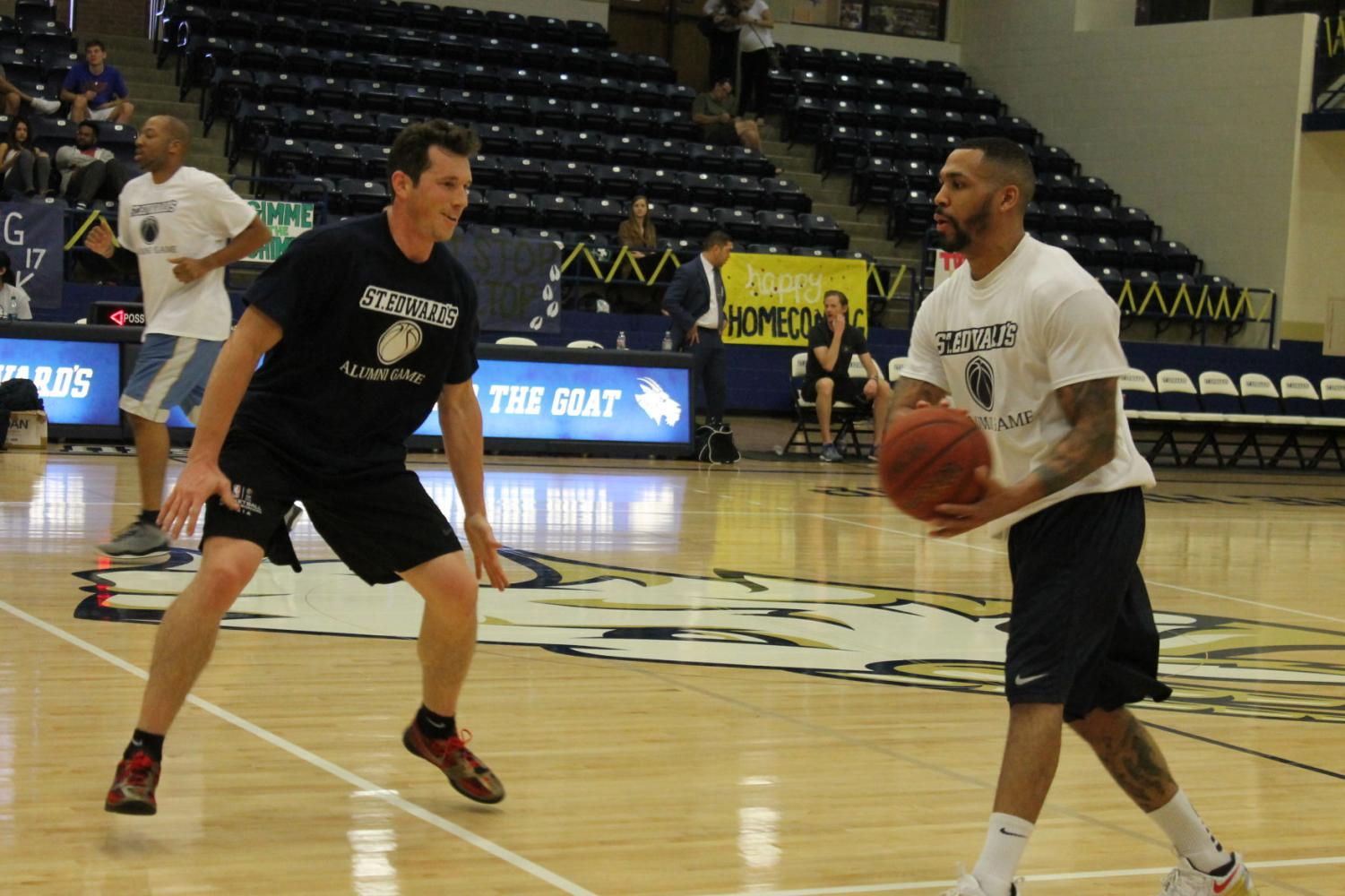 Taylor Land (left) guards John Rutherford (right) at the men's basketball alumni game Feb. 18.