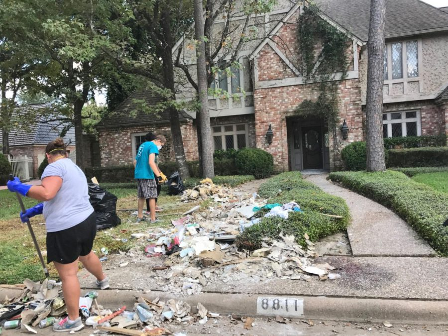 Campus+Ministry+volunteers+rake+and+shovel+debris+onto+the+street+from+a+water-damaged+home+in+Spring%2C+Texas%2C+on+Sept.+16.