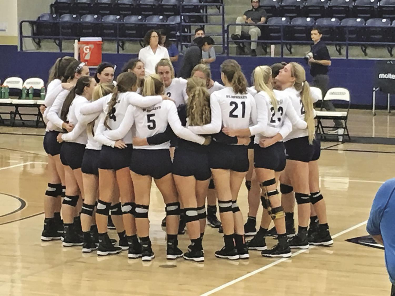 SEU volleyball huddles after winning their conference opener.