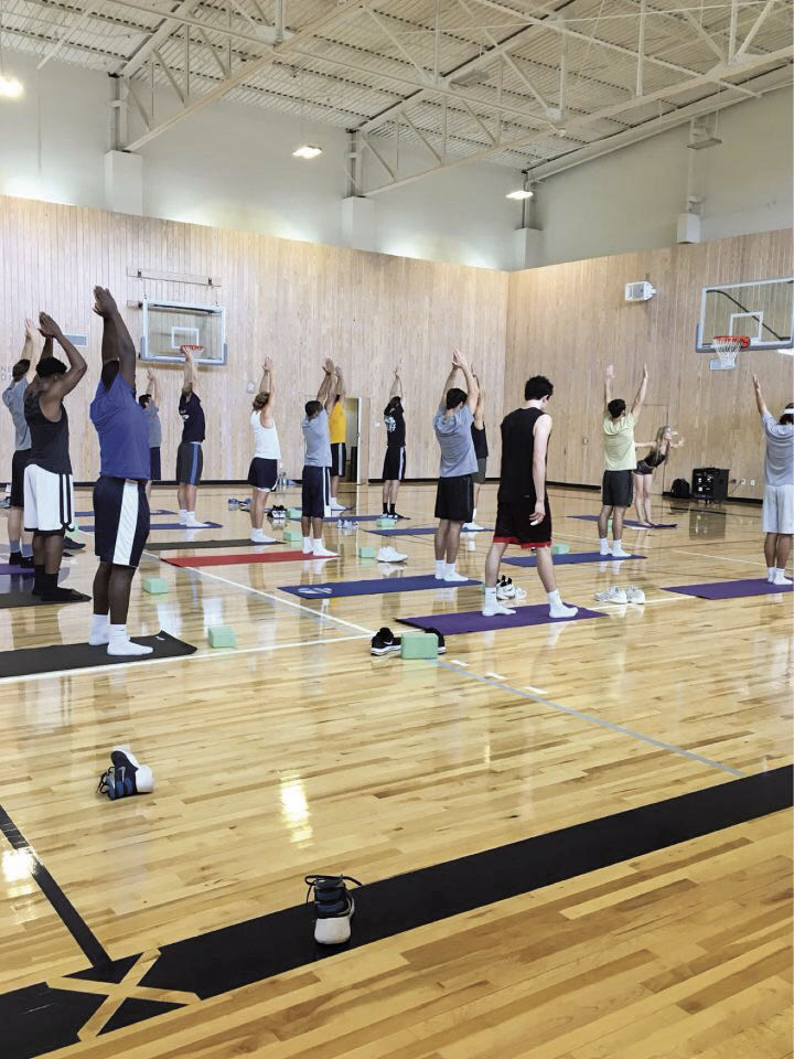 The men's basketball team is guided through a yoga flow, a series of poses that synthesize for a unified purpose in the body