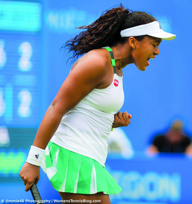 Naomi Osaka unleashes victory yell after a tennis match.