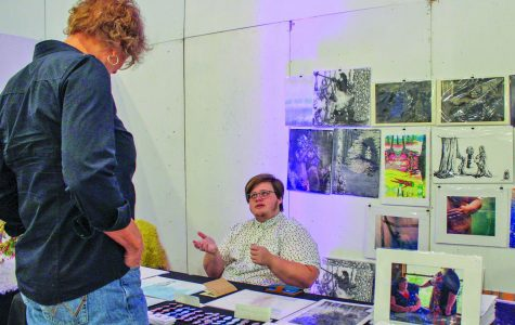 Printmaker Nelvin Cecil Howell discusses some of (their) artwork with a guest.