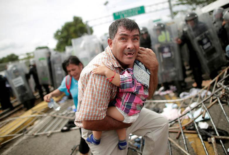 A father cradles his child as violence breaks out between police and the caravan.