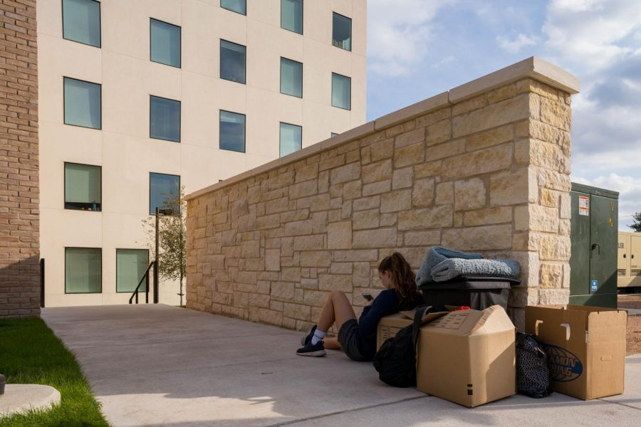 A student waits with her luggage outside the Pavilions residence hall. Students from three of the four wings will be unable to reside in the building for the remainder of the semester.