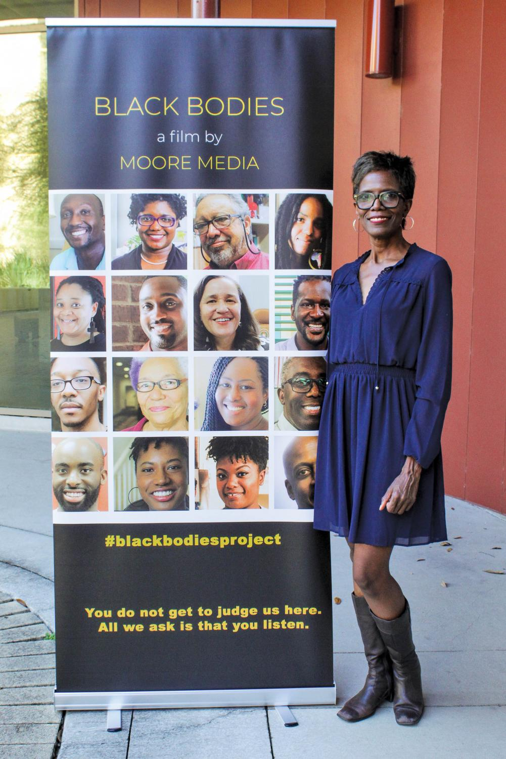 Charlotte Moore poses by the 'Black Bodies Project' poster. This is Moore's first film.