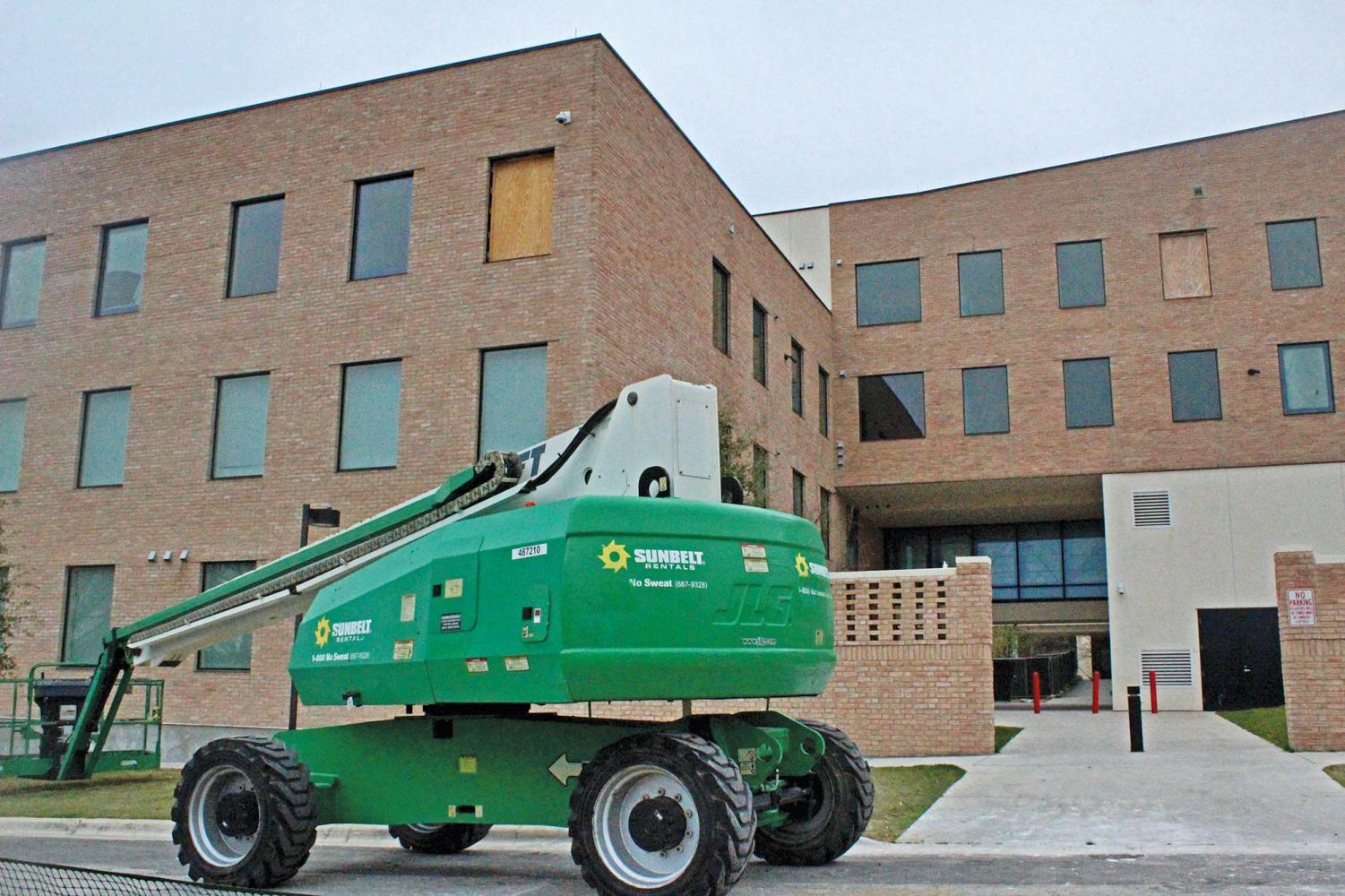 A construction vehicle sits parked next to the Pavilions residence hall. Administration claims it will be available for student living in time for the coming school year.