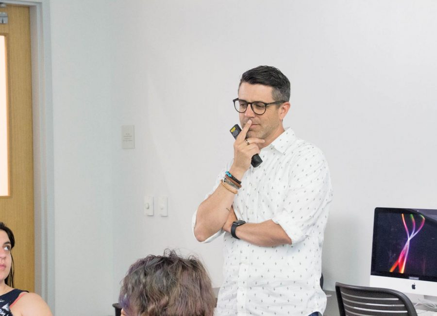 Professor Manuel Piña teaches a group of students. Piña believes sharing stories and elements from his personal life with students helps facilitate their education.