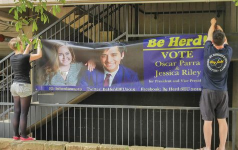 Students set up campaign sign for presidential/vice presidential candidates Oscar Parra and Jessica Riley.