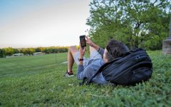 St. Edward's student lounges with his phone by the soccer field.