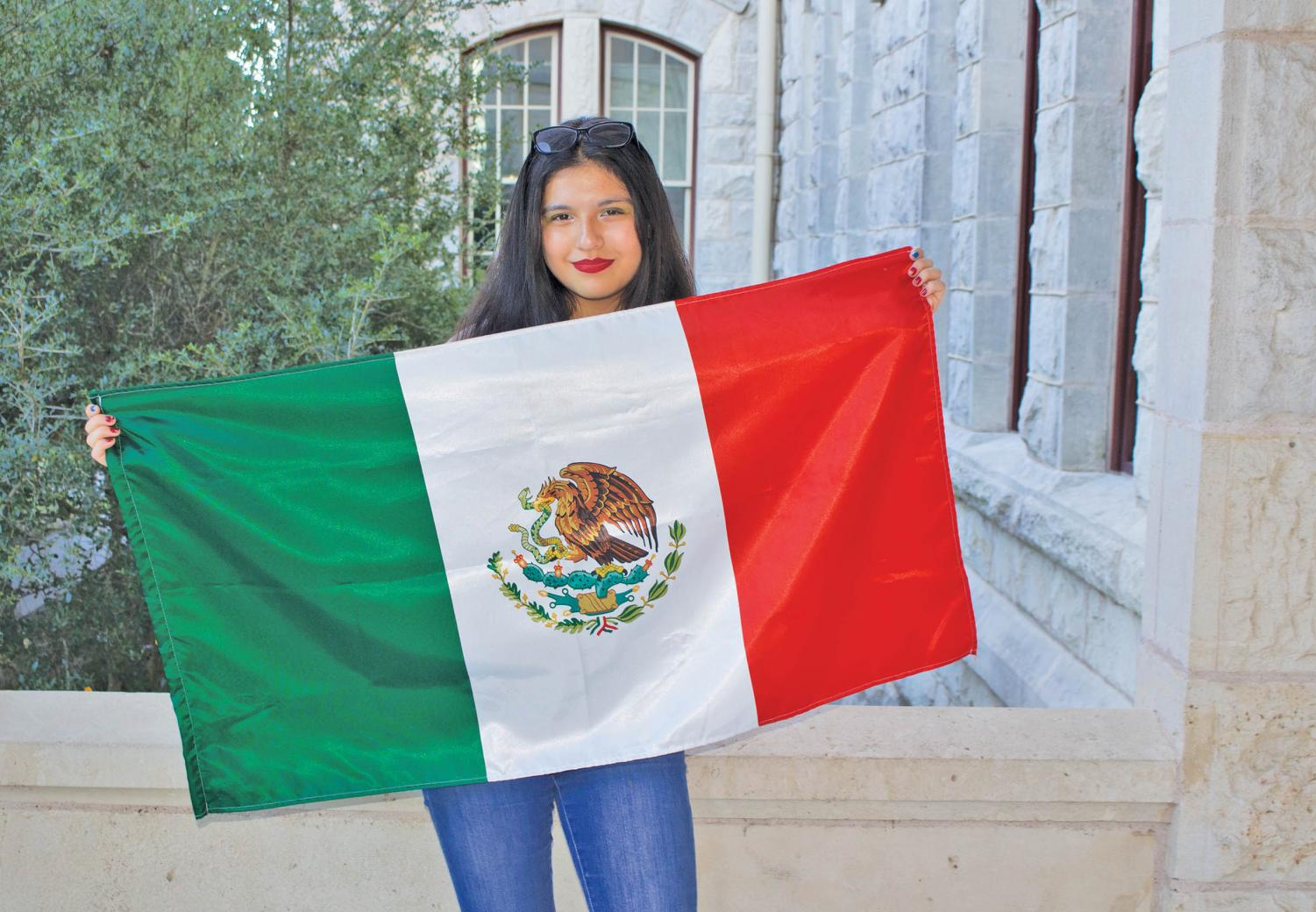 Isabel Herrera holds Mexican Flag in honor of her parents from Mexico.