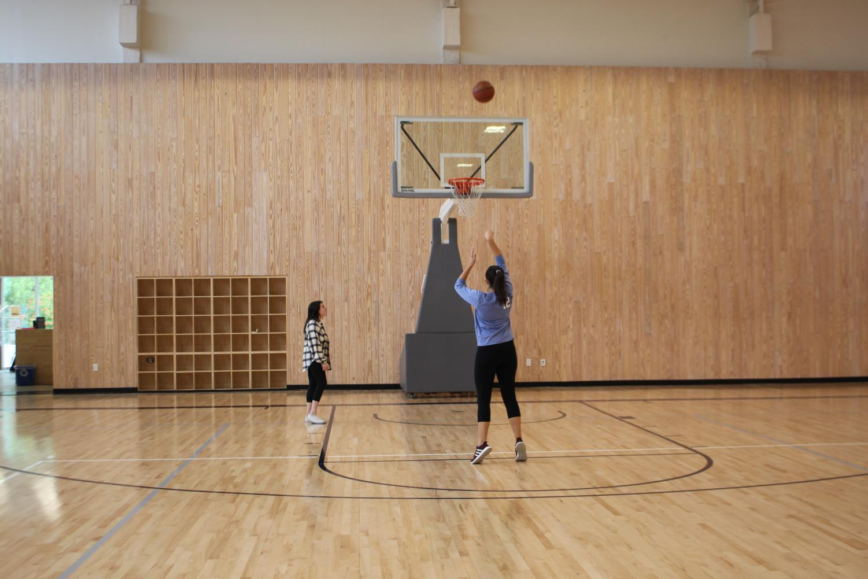 Club co-president Elyse Wick practices her free throw routine as fellow co-president Izzy Garza prepares to grab a rebound.