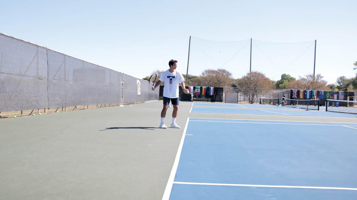 Junior tennis player Luis Diaz prepares to play a forehand during a team practice. Over his career on the hilltop, Diaz has accumulated a singles record of 29-13.