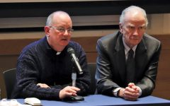 (Left to right) Father Peter Walsh, Director of Campus Ministry, and President Martin sit on the panel for the annual meeting. Martin emphasized the Holy Cross mission at the start of the event.