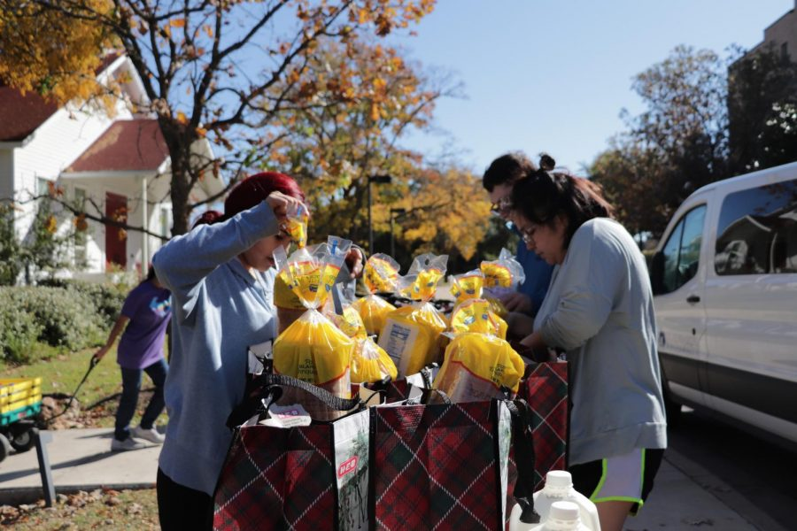 Volunteers fill donation bags with milk, bread, eggs and other perishables. The donations went to 50 Austin-area families.