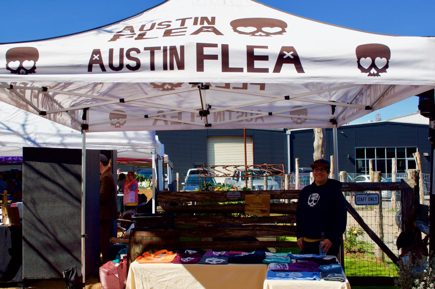 """Garcia, an Austin Flea employee, is seen selling T-shirts. """"Everything here is unique. Jewelry tends to have the most people creating and selling, so we try to balance it out by also including organic soaps, clothing, food, original designs, and even CBD joints. We really feature a little bit of everything,"""" Garcia said."""