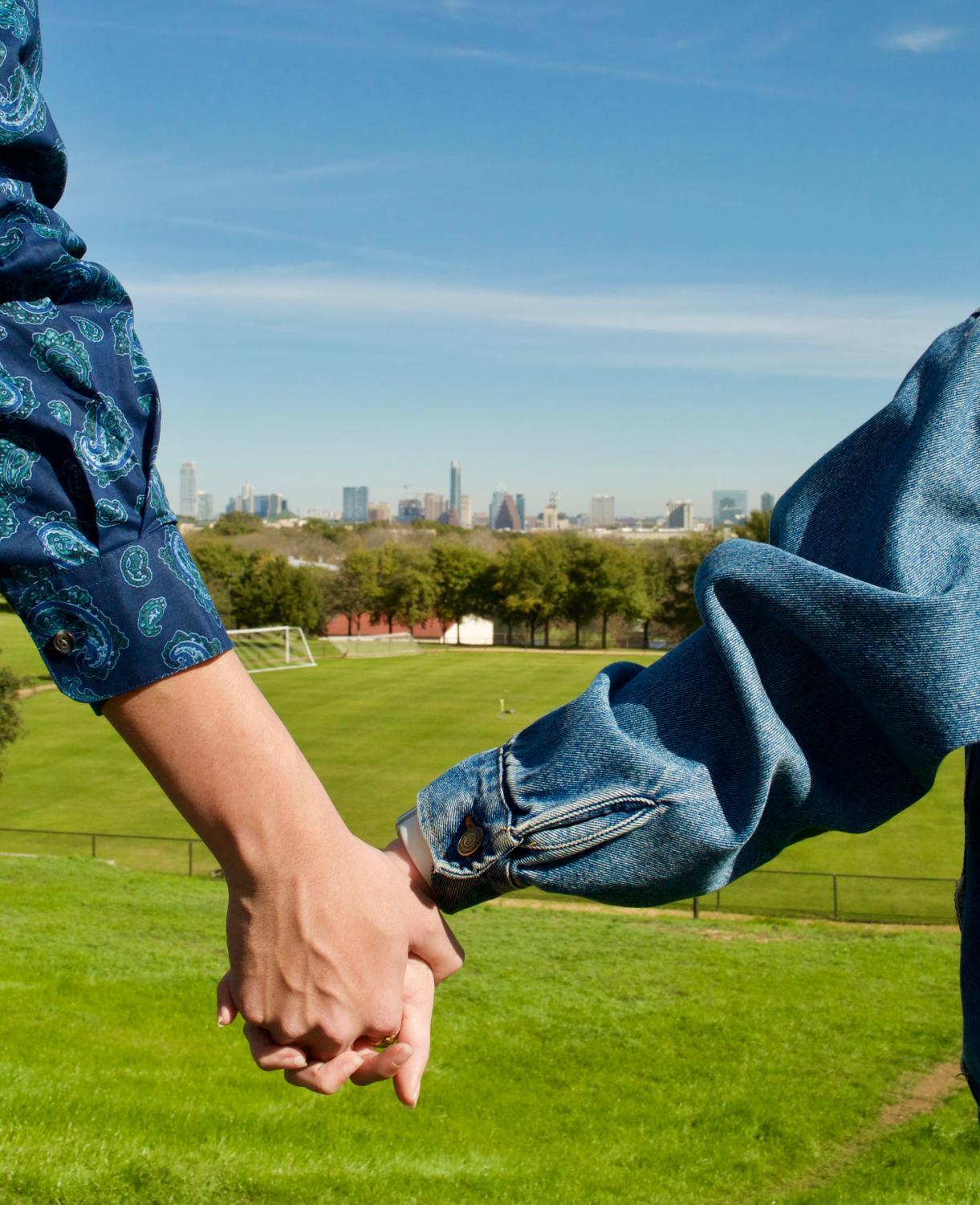 Sophomores Maddie Benbenek and Pete Cervantes hold hands in front of campus' popular view of Austin's skyline.
