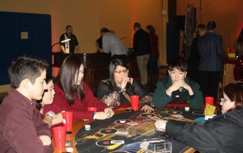 A visiting family plays blackjack at the casino section of the Homecoming Bash. Guests could trade in tokens won during gambling for raffle tickets for a chance to win prizes such as AirPods, a FitBit and more.