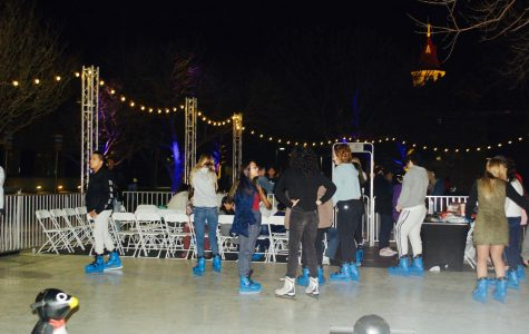 Students enjoy the ice-rink in blue skates with a view of the top of Main Building. Ice skating was free for all, and free donuts were provided as well. Students had a full weekend with the Homecoming Bash, the tailgate, a magician, hypnotist and ice skating.