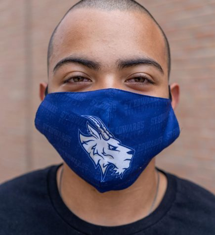 St. Edward's student Isaiah Bass is following guidelines by wearing his Topper mask. Masks like these can be purchased at St. Edward's bookstore.