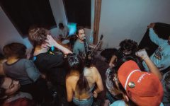 San Martin (middle) can be seen performing at a DIY-style concert. These types of performances are common in the underground San Antonio music scene.