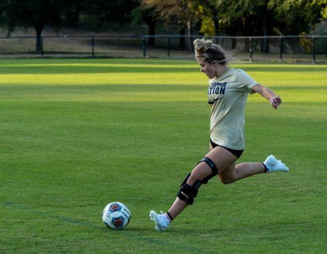 Freshman Katelyn Smith strikes a ball on the Lewis-Chen Family Field on campus. The midfielder is part of the women