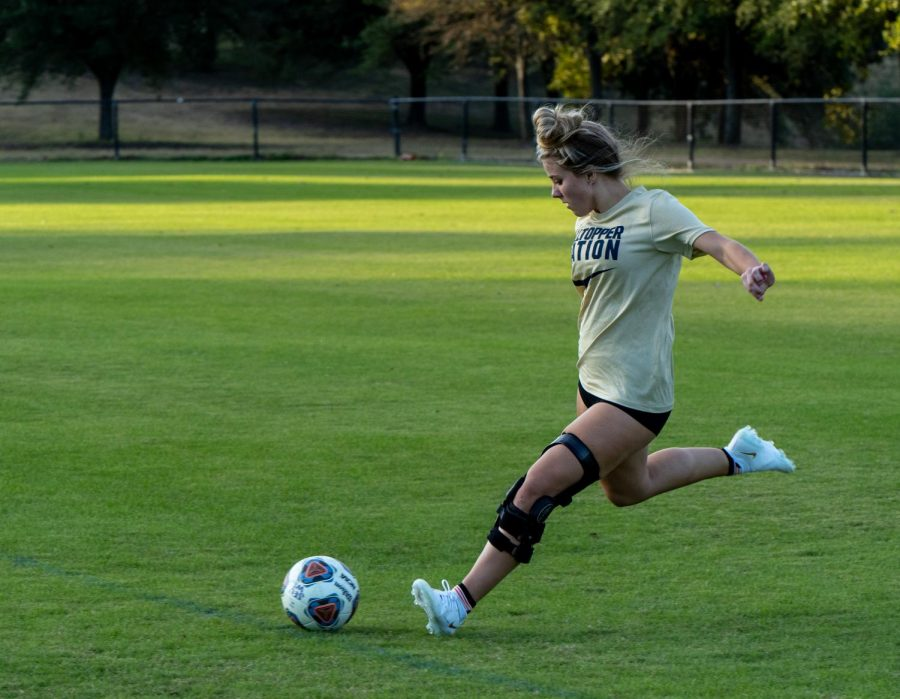 Freshman Katelyn Smith strikes a ball on the Lewis-Chen Family Field on campus. The midfielder is part of the womens soccer team at St. Edwards that last year had an overall record of 13-7-2.