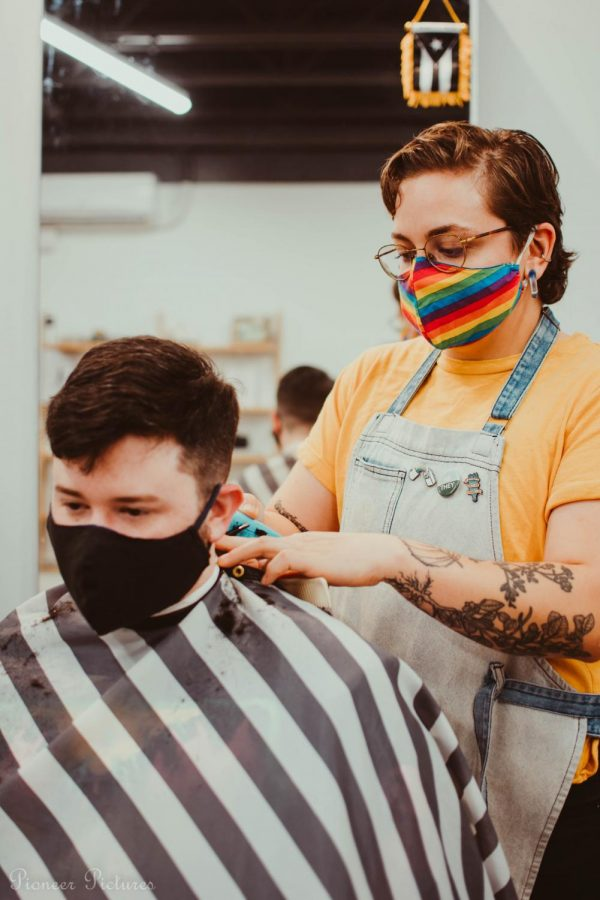 Customer Noah gets a stylish fade from The Barbashop founder and owner Ru. Customers who support and visit The Barbashop are greeted with cold beer and conversation during a trim.