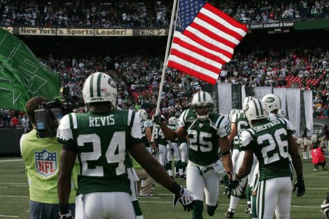 Kerry Rhodes of the New York Jets carries an American Flag on to the field during pre-game introductions in 2009. The issue of mandatory patriotism and playing the national anthem before games has become a hotly discussed topic in recent years.