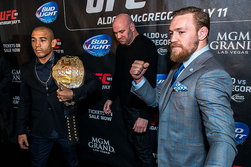McGregor (right), Dana White (middle) and José Aldo (left) in London as part of the World Tour promoting UFC 189 in March 2015. The Irishman's loss to Poirier at UFC 257 was the first time he had been knocked out in his UFC career.