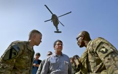 As a Black Hawk helicopter rumbles overhead, Deputy Secretary of Defense Ashton B. Carter speaks with Brig. Gen. Ron Lewis, right, during a visit to bases in Afghanistan, May 13.