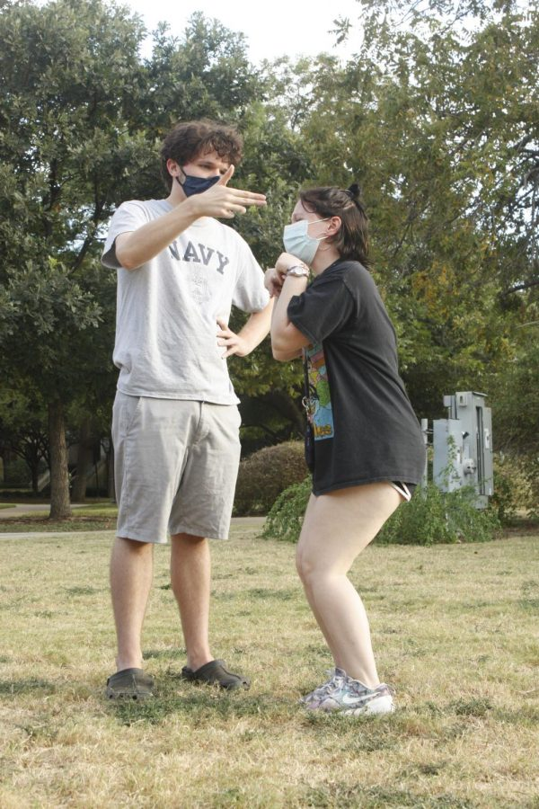 """St. Edwards University students Coleman Hahn (left) and Gwendalyn Waggoner (right) playing """"Freeze,"""" an improv game  in which two players enact a scene and switch with other players when told to freeze."""